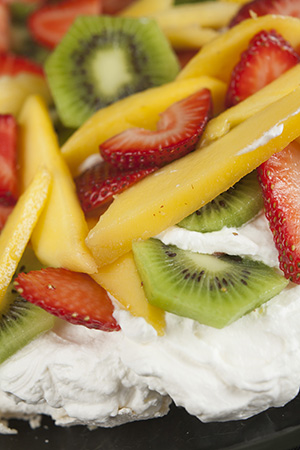 Pavlova with strawberries, kiwi fruit, and mango